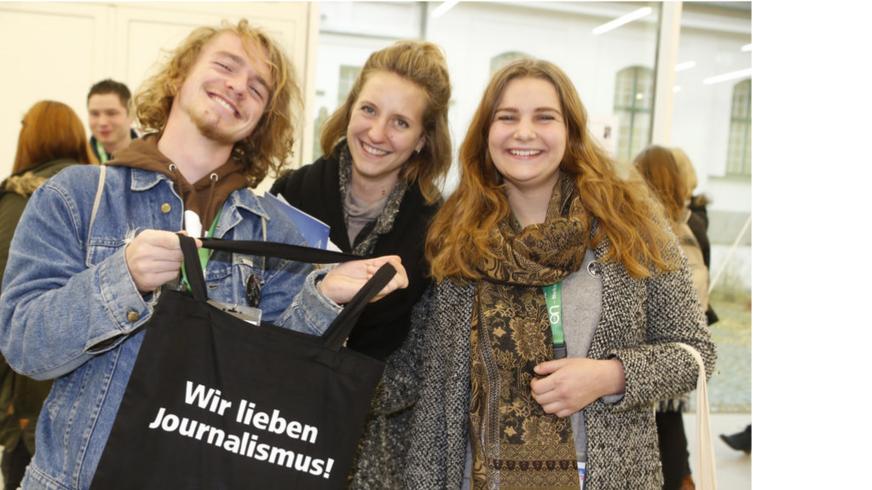 """Ein junger Mann und zwei junge Frauen halten einen schwarzen Jutebeutel mit der Aufschrift """"Wir lieben Journalismus!"""" in der Hand"""