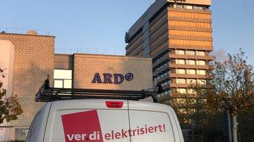 """Weißer Transporter mit ver.di-Logo und Aufschrift """"ver.di elektrisiert"""" in rot steht vor dem Sendegebäude des NDR in Hamburg"""