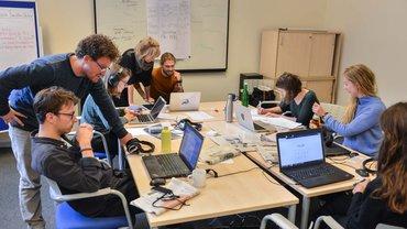 Schülerinnen und Schüler der Evangelischen Journalistenschule sitzen an einem großen Tisch und arbeiten
