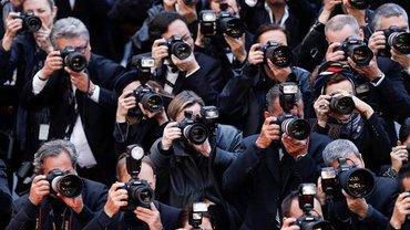 Zahlreiche schwargekleidete Männer und Frauen richten Ihre Kameras vor den Augen auf das Objektiv des Fotografierenden.