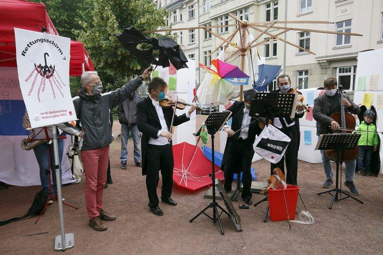 Musiker musizieren unter einem durchlöcherten schwarzen Regenschirm