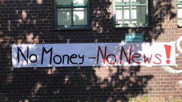 """auf weißem Banner steht """"No money-no news"""". Das Banner ist an eine Ziegelwand angeheftet"""